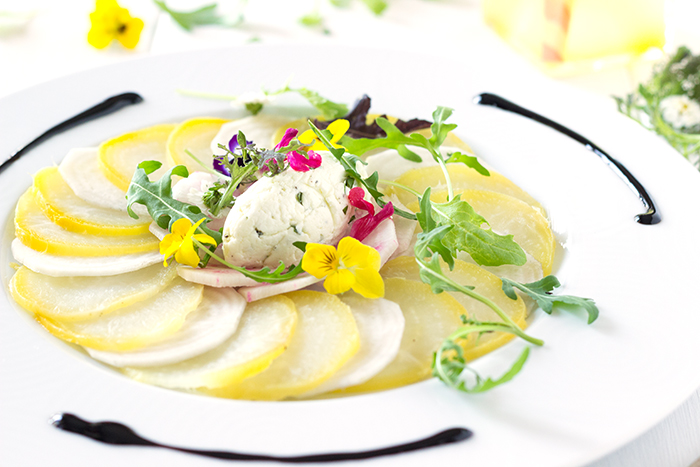 Yellow beetroot carpaccio with fresh goat cheese quenelles